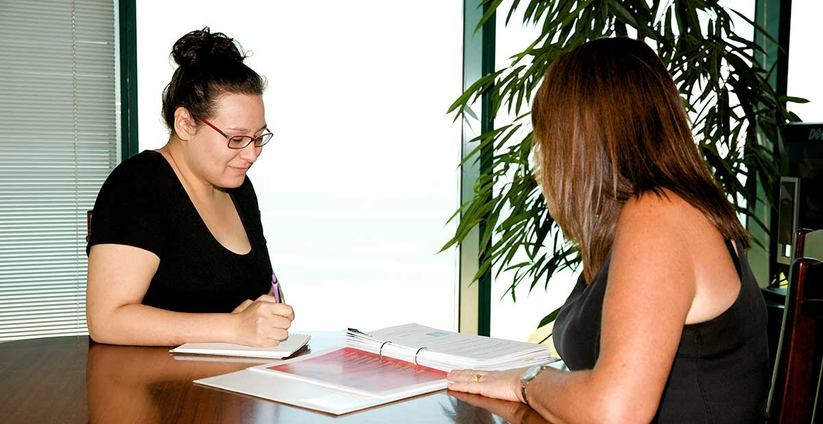 Two women sitting at table reviewing content of a folder