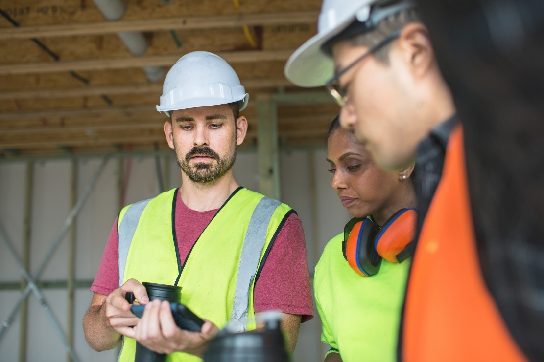 Workmen viewing a tablet device
