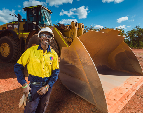 Workman standing in front of heavy machinery