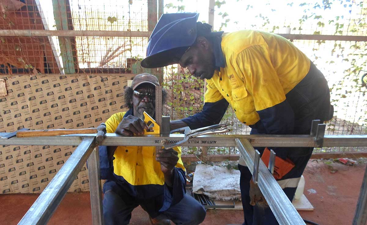Workmen measuring steel