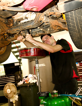 Young man working on the suspension of a car during the 2000
