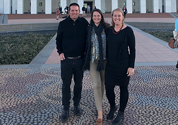 Paul Armstrong, Maddy Clonan and Meg Humphrys standing in front of Parliament House, Canberra