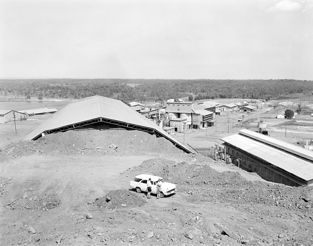 Rum Jungle mine site with stockpiled ore in foreground and White's flooded open cut in the background (1963). National Archives of Australia: A12111, 1/1963/10/40