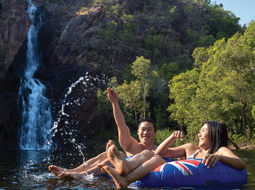 Two people floating in front of a waterfall