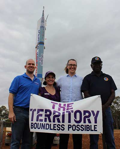 Group of people standing in front of rocker with The Territory banner