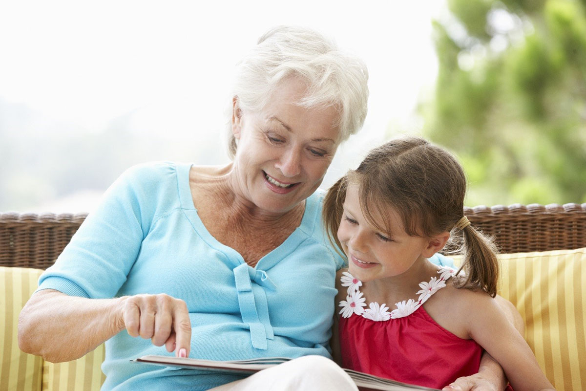 Elderly woman and granddaughter reading a book