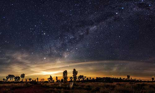 Sun setting in distance with stars in the sky at the foreground